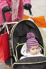 Mother walking with baby in stroller, close up on baby