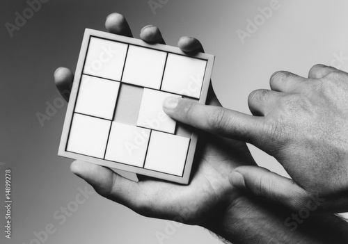 Hands holding slide puzzle, b&w, close-up