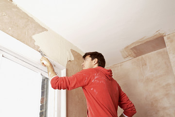 Man scraping paint off wall in unrenovated room, low angle view