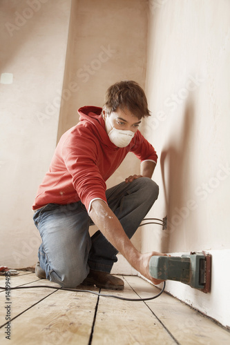 Man wearing face mask, sanding wall in unrenovated room, low angle view