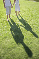 Couple holding hands walking on grass, low section