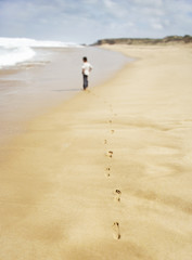 Boy walking along sandy beach, back view