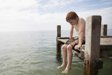 Pre-teen boy sitting on end of pier with feet in water, portrait
