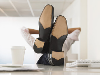 Businessman with Feet Up on Desk, obscured face
