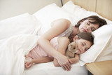Mother and daughter sleeping in bed, portrait