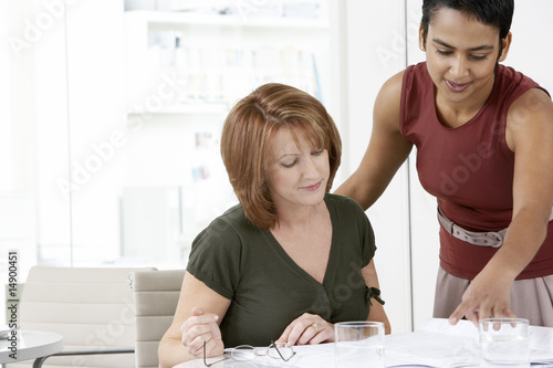 Two women conferring at office desk