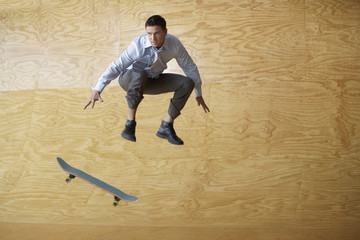Man crouching, jumping from skateboard, mid-air, in front of interior wall