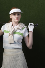 Woman with visor holding golf club behind shoulders, portrait