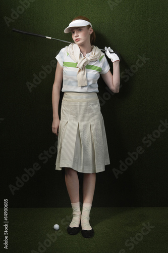 Woman in visor holding golf club behind shoulders, portrait