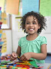 Girl assembling  puzzles in classroom, portrait