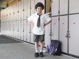 Elementary schoolboy standing by school lockers, portrait