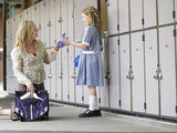 Mother packing daughters school bag near school lockers