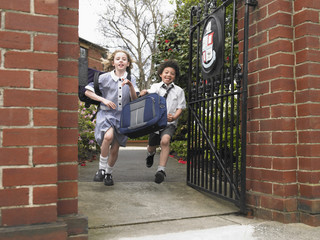 Elementary students running out through school gate