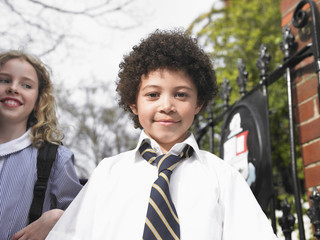 Elementary school students standing by school gate, portrait