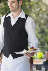 Waiter carrying slice of pie at outdoor cafe