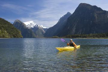 Man paddling kayak in mountain lake