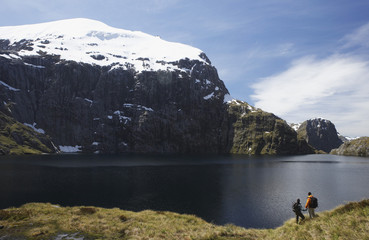 Two hikers looking at mountain lake