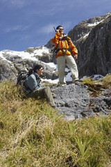 Man using walkie-talkie while a woman rests on rock on hiking trail in mountains