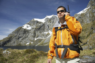 Hiker using walkie-talkie on mountain trail