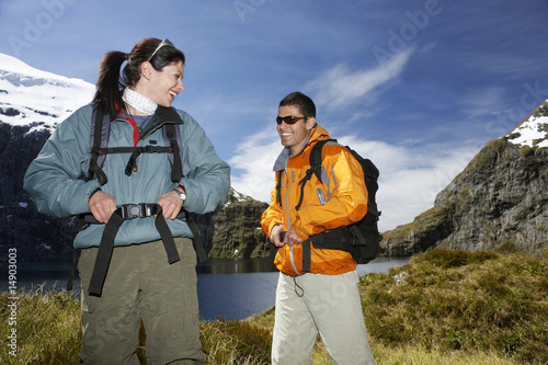Two hikers smiling on mountain peak
