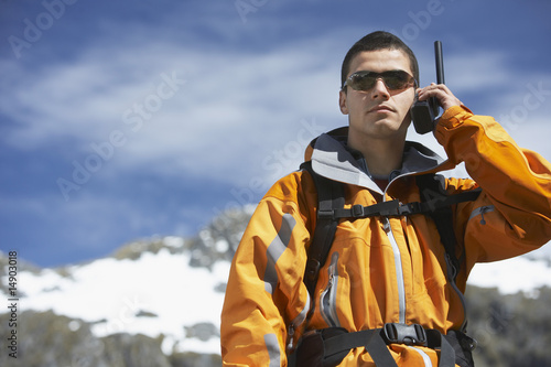 Man using walkie-talkie on mountain peak