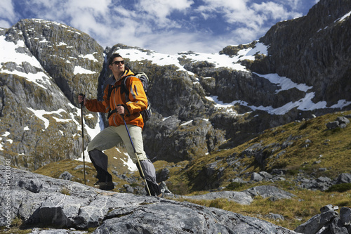 Hiker with walking sticks in mountains