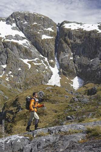 Hiker climbing trail in steep mountains