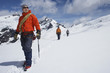 Three hikers joined by safety line in snowy mountains