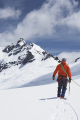 Hiker connected to safety line in snowy mountains, back view