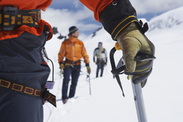 Hikers using walking sticks in snowy mountains, mid section on front man