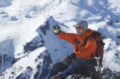 Mountain climber taking a picture on mountain peak