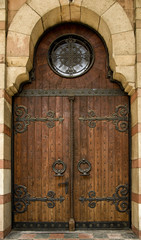 Church doorway with wooden doors and intricate metal hinges.