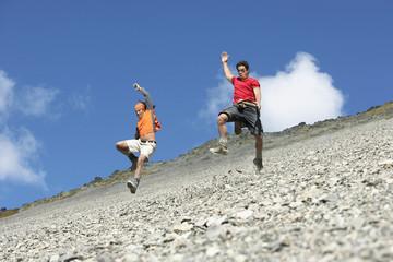 Two men jumping down screen field