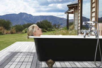Woman taking bath on porch by mountains