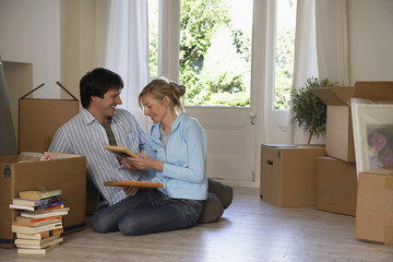 Couple sitting on floor at home with boxes and books