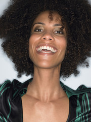 Woman with afro, smiling, head and shoulders, in studio