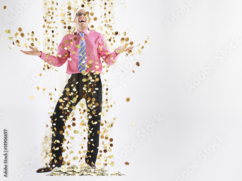 Man in glasses laughing with gold coins falling to floor