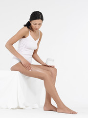 Young Woman in underwear Applying Body Lotion to thighs