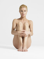 Nude Young Woman sitting with hands on knees, portrait