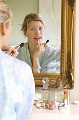 Woman in bathrobe sitting, Applying Make-up, looking in mirror
