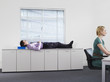 Businessman sleeping on office cabinets near woman working