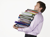 Male office worker carrying heavy binders, on white background