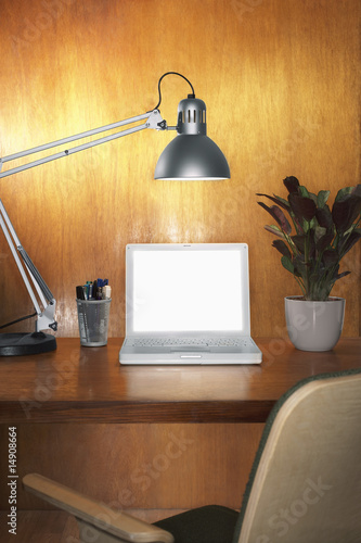 Laptop with blank screen and other items on desk with chair