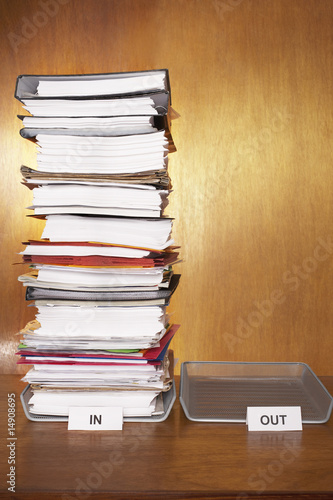 Inbox with stack of paperwork, empty outbox on desk