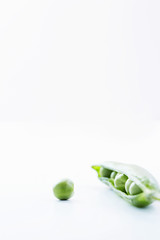 Open pea pod containing peas and single pea, close-up