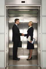 Businesspeople shaking hands in Elevator, side view