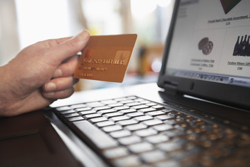 Man holding credit card in front of laptop, close up