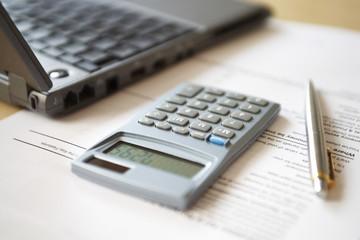 Calculator lying next to laptop, close-up
