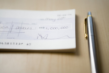 Cheque for one million dollars lying next to pen on table, close-up