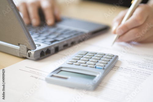 Woman using laptop and calculator, close up